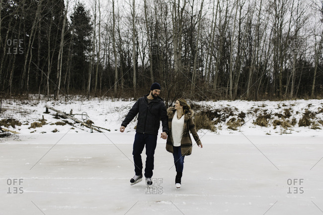 Couple skating on frozen lake, Whitby, Ontario, Canada