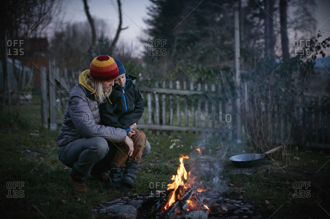 Mature woman and son crouching to watch garden campfire at dusk