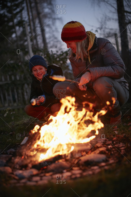 Mature woman and son toasting marshmallows on garden campfire at dusk