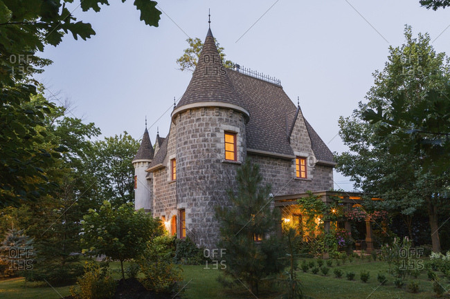 2006 reproduction of a 16th century grey stone and mortar Renaissance castle style residential home facade, at dusk, in summer, Quebec, Canada