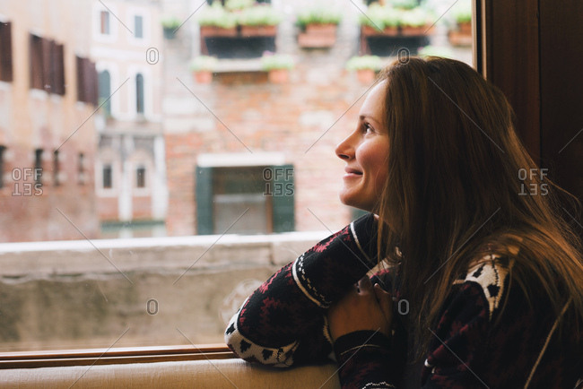 Woman looking out window, Venice, Italy