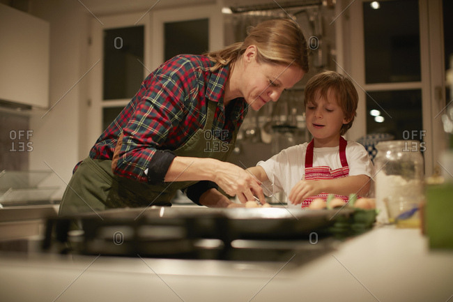 Mature woman helping son with baking on kitchen counter