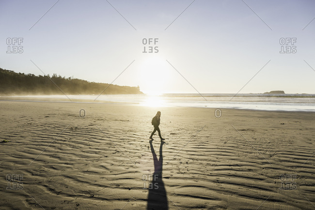Woman strolling on Long Beach at sunrise, Pacific Rim National Park, Vancouver Island, British Columbia, Canada