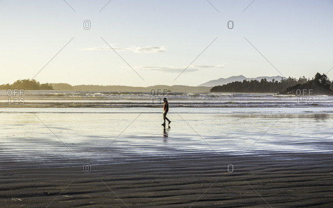 Man strolling on Long Beach at sunrise, Pacific Rim National Park, Vancouver Island, British Columbia, Canada
