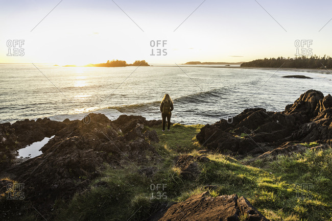 Woman watching sunset from coast, Pacific Rim National Park, Vancouver Island, British Columbia, Canada