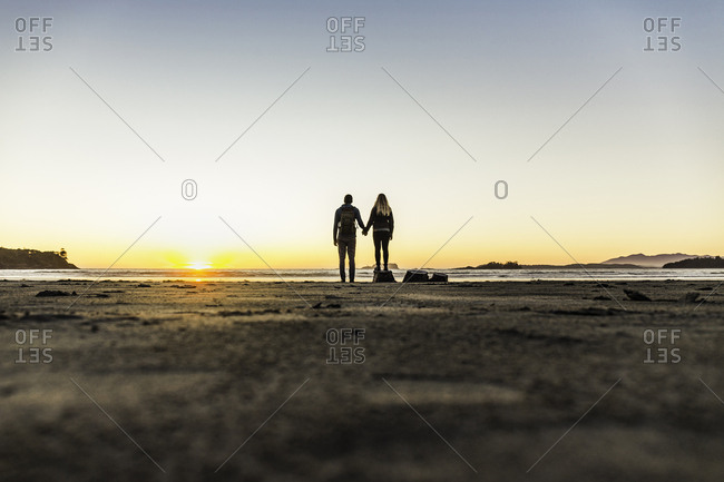 Couple watching sunset from Long Beach, Pacific Rim National Park, Vancouver Island, British Columbia, Canada