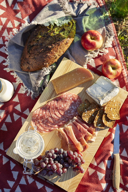 Overhead view of fresh picnic food with cheese, salami and grapes