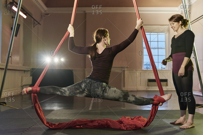Two young female aerial acrobats practicing the splits on silk rope
