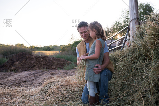 Father and daughter standing together on farm, daughter holding hay
