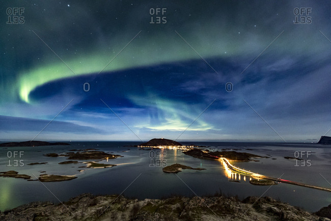 Northern lights (Aurora Borealis) in the night sky over famous Sommaroy Bridge crossing from Kvaloya Island to Sommaroy island in autumn, Arctic Norway