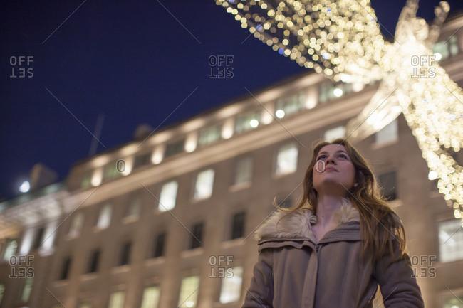 Young woman enjoying Christmas lights, Regent Street, London, UK