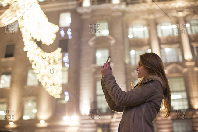 Young woman photographing Christmas lights, Regent Street, London, UK