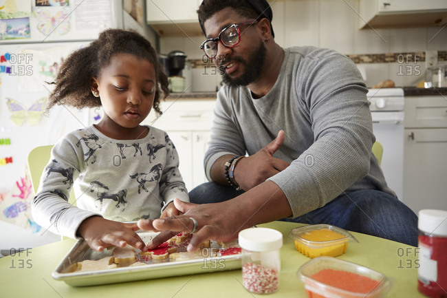 Father and daughter decorating unbaked cookies