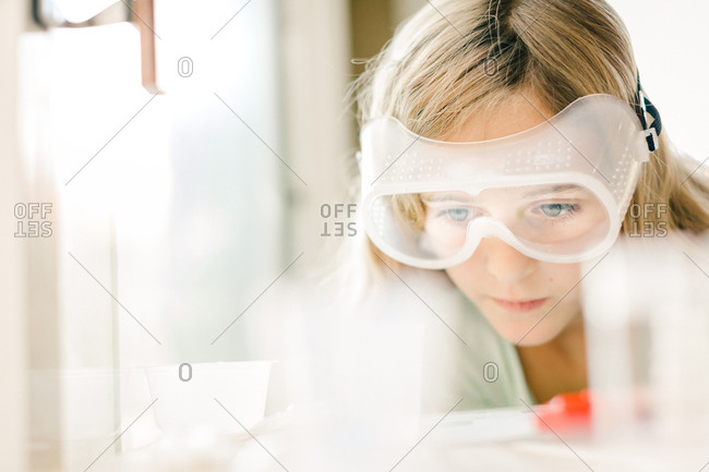 Girl doing science experiment, watching through safety goggles