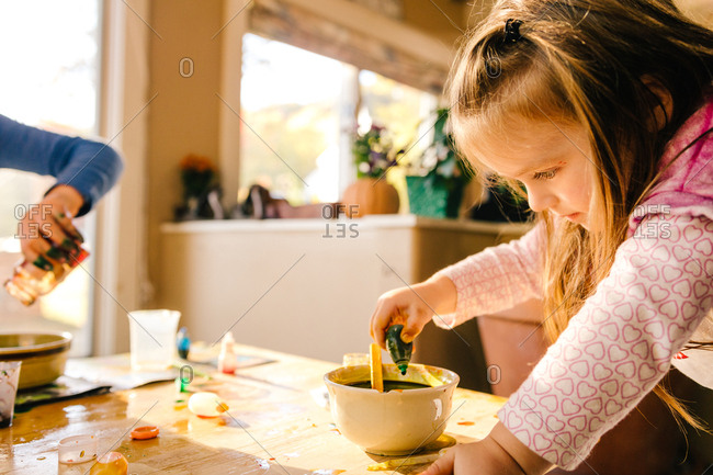 Girl doing science experiment, dropping green liquid into bowl