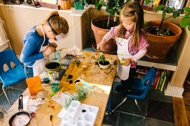 Two girls doing science experiments at messy table