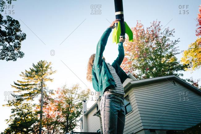 Girl throwing toy rocket upward toward blue sky