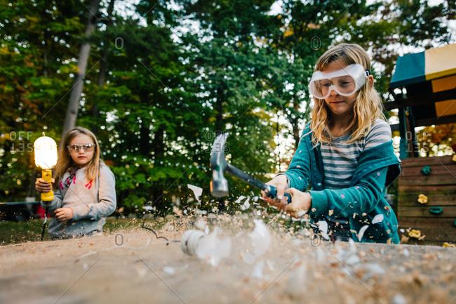 Girl smashing lightbulb with hammer on garden table at dusk