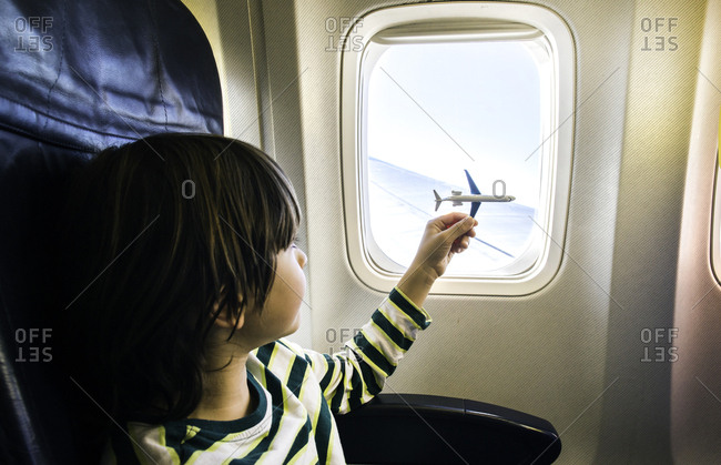 Boy playing with toy airplane at airplane window