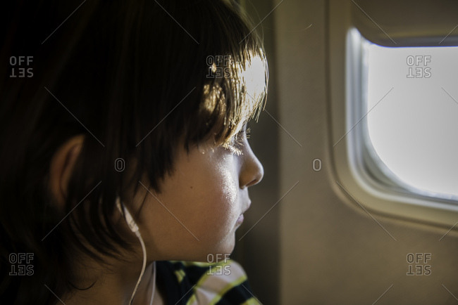 Boy on airplane looking through sunlit airplane window