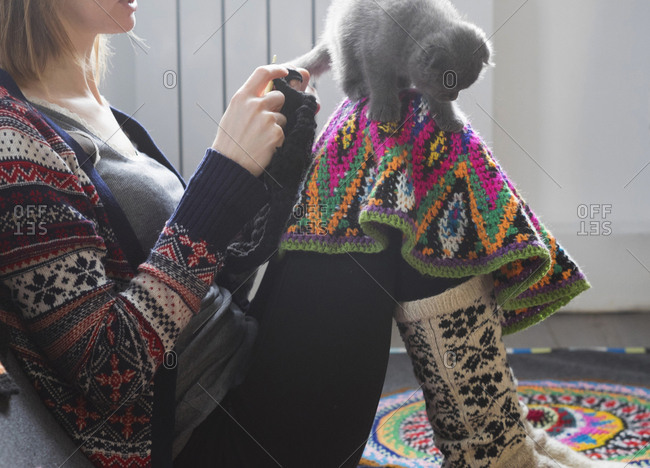 Woman sitting on floor crocheting with kitten balancing on her knee
