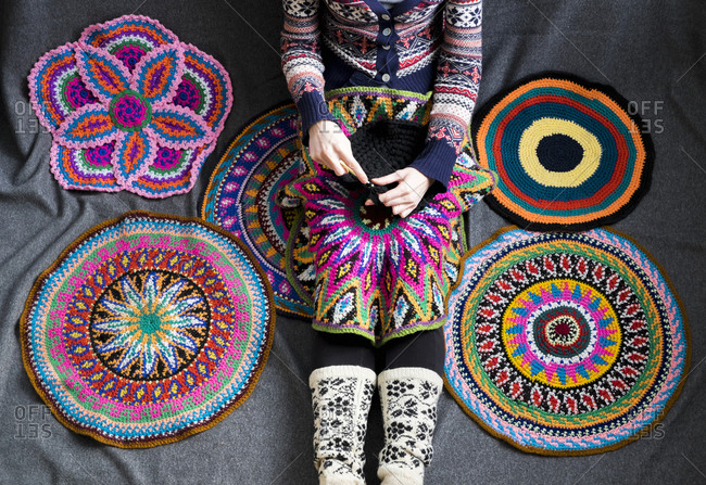 Neck down view of woman sitting on floor crocheting, surrounded by crochet circles