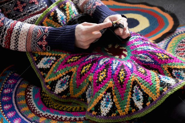 Mid section of woman sitting on floor crocheting, surrounded by crochet circles