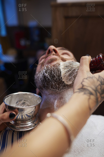 Woman applying shaving cream to man's beard
