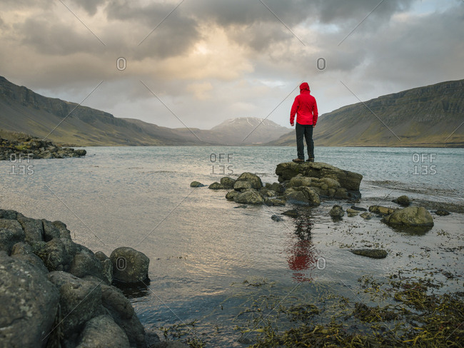 Man at edge of water, Hvalfjordur, Iceland