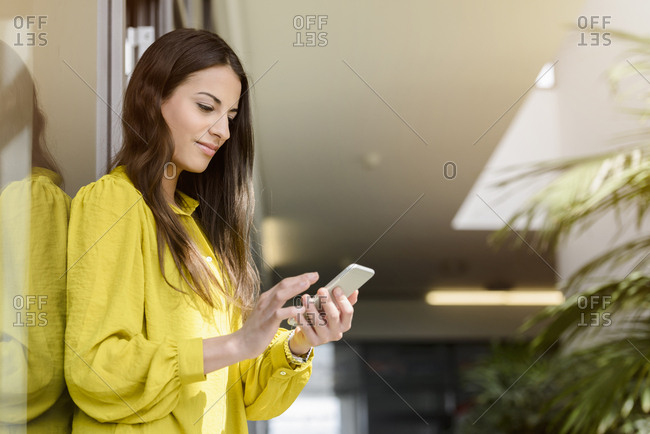 Young businesswoman using smartphone touchscreen in office atrium