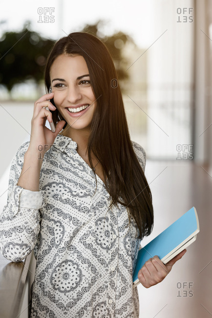 Young businesswoman in office corridor talking on smartphone