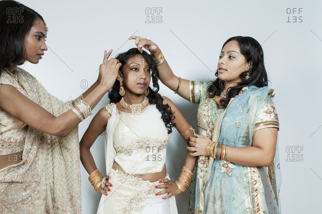 Two young women helping friend dress in traditional Indian costume