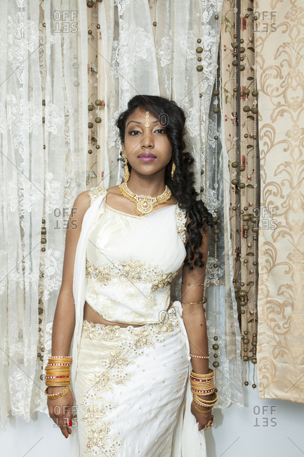 Portrait of young woman in front of net curtain dressed in traditional Indian costume