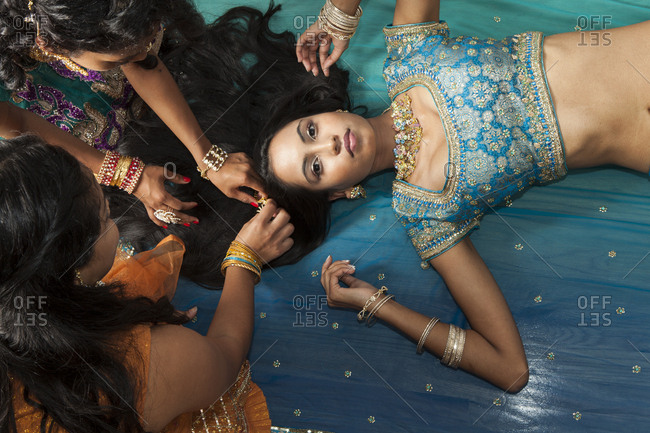 Overhead portrait of young woman in traditional Indian costume having hair dressed by friends