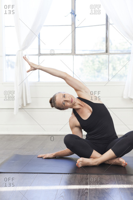 Portrait of young woman cross legged on yoga mat practicing yoga
