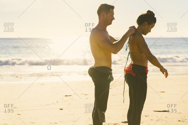 Man helping girlfriend put on wetsuit at Newport Beach, California, USA