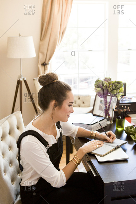 9be465a2d60c24 ... Female fashion and lifestyle blogger writing in notebook at desk