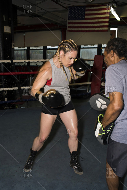 Trainer training female boxer with boxing mitt in boxing ring
