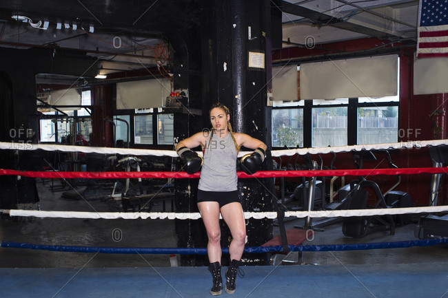 Portrait of female boxer leaning against boxing ring ropes, full length