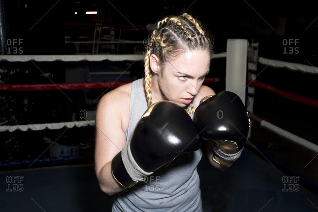 Female boxer poised for sparring in boxing ring