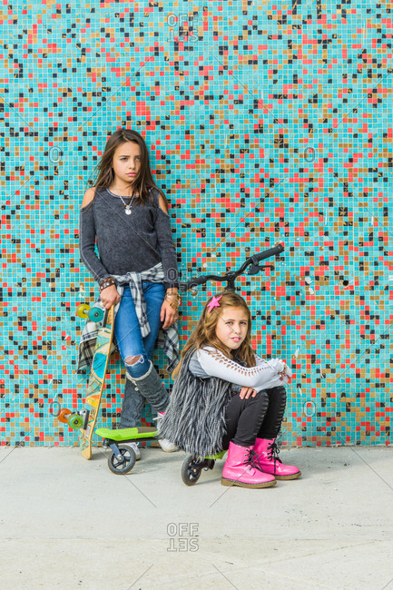 Portrait of two sisters with skateboards and scooter by multi-colored urban wall