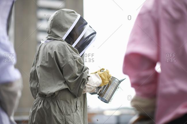 Beekeeper holding bee smoker