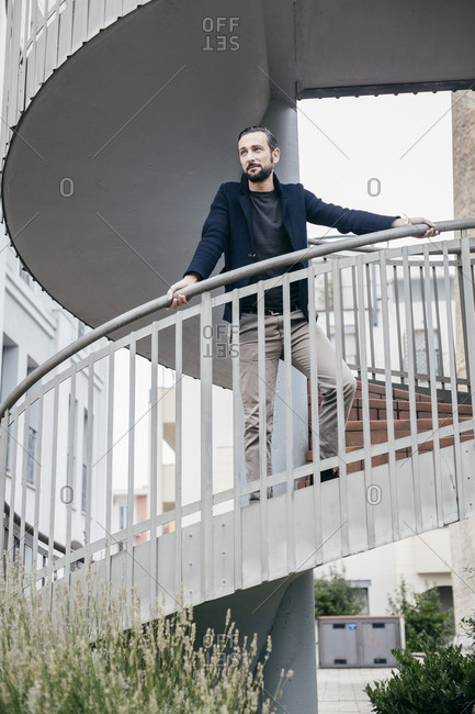 Man on spiral staircase looking away