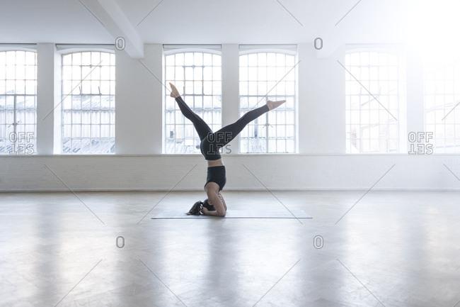 Woman in dance studio doing headstand