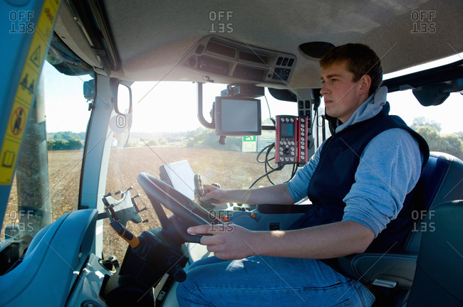 Young man driving tractor using global positioning system