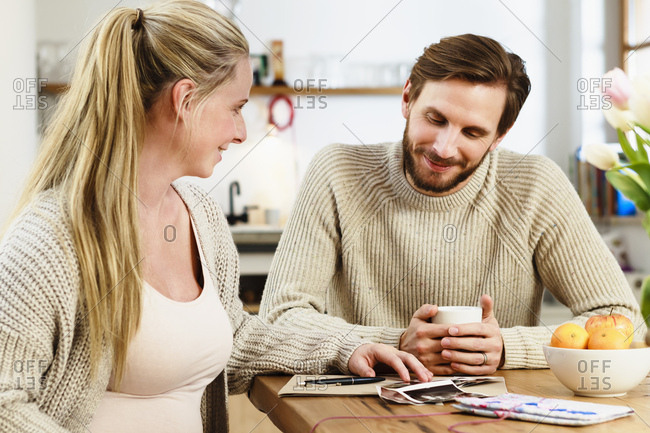 Pregnant mid adult couple looking at pregnancy scans on table