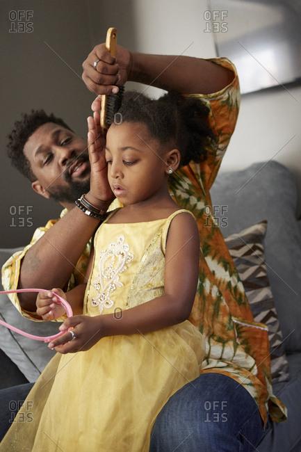 Man on sofa brushing daughter's hair for princess tiara