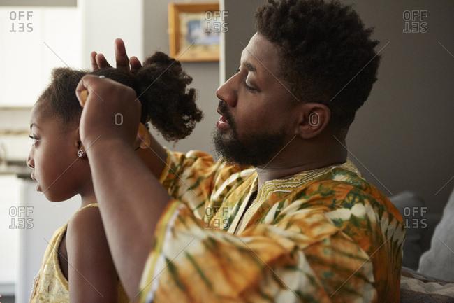 Man brushing daughter's hair in living room