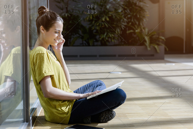 Young female student sitting cross-legged outdoors talking on smartphone