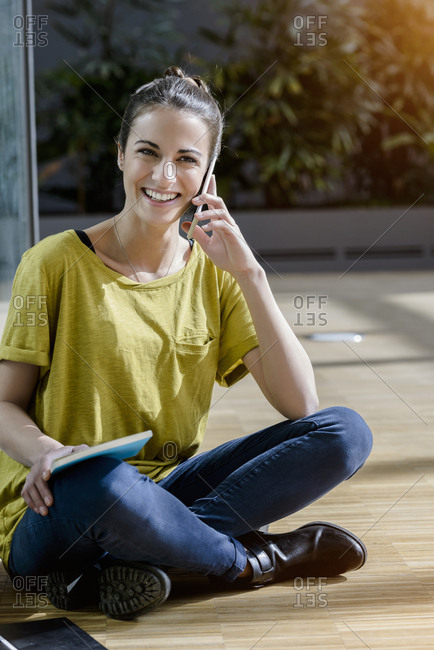 Portrait of young female student sitting cross-legged outdoors talking on smartphone